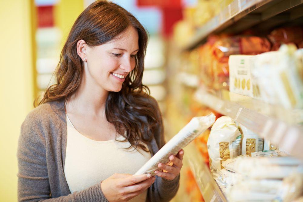 Lächelnde Frau im Supermarkt schaut auf eine Packung Nudeln