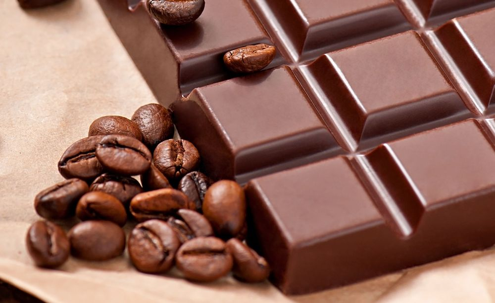 Chocolate and coffee beans on beige paper background