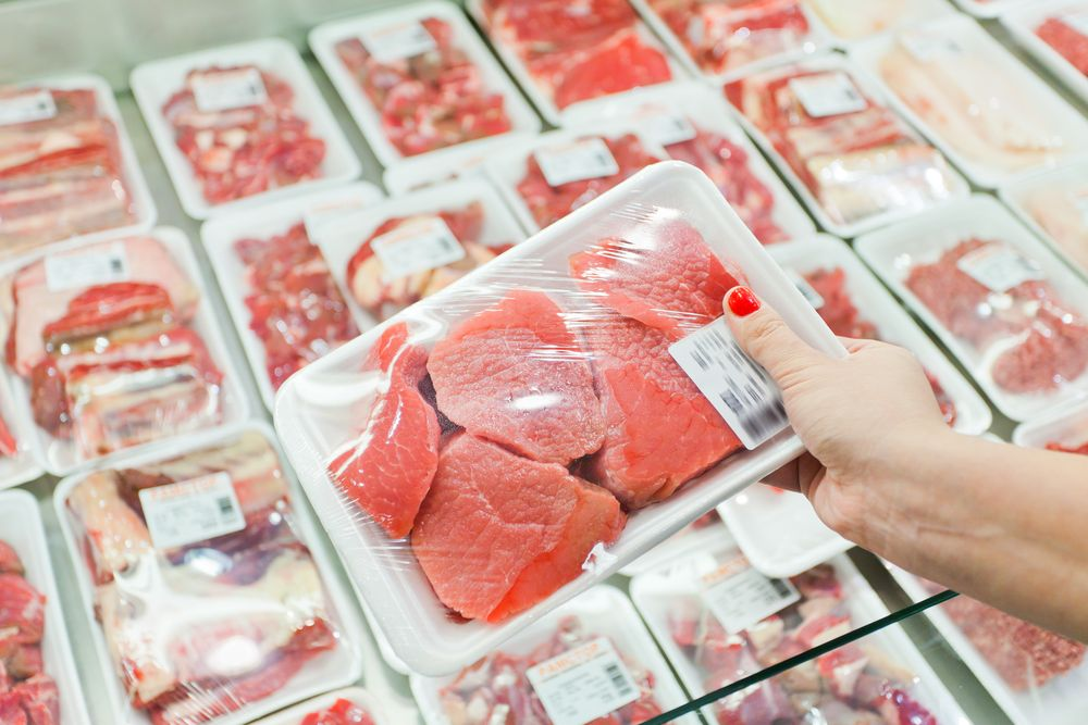Packaged meat with woman hand in the supermarket